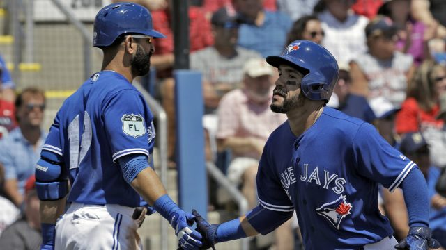 Toronto-Blue-Jays'-Devon-Travis,-right,-shakes-hands-with-on-deck-batter-Jose-Bautista-after-scoring-on-an-RBI-single-by-Troy-Tulowitzki-off-Boston-Red-Sox-starting-pitcher-Drew-Pomeranz-during-the-second-inning-of-a-spring-training-baseball-game-Friday,-March-24,-2017,-in-Dunedin,-Fla.-(Chris-O'Meara/AP)