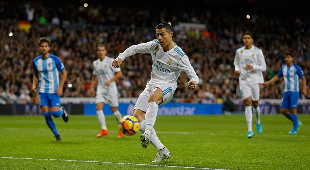 Cristiano Ronaldo Shoots To Score His Sides Third Goal Against Malaga During The Spanish La Liga Match Between Real Madrid And Malaga At The Santiago