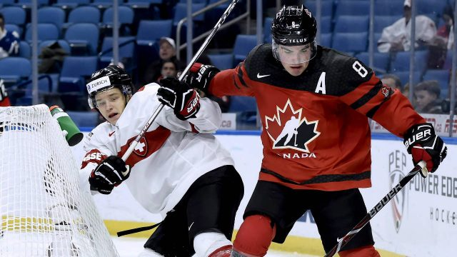 Canada's-Dante-Fabbro-(8)-vies-for-control-of-the-puck-with-Switzerland's-Philipp-Kurashev-(23)-as-Switzerland's-Philip-Wuthrich-(30)-looks-on-during-second-period-quarter-final-IIHF-World-Junior-Championships-hockey-action-in-Buffalo,-N.Y.,-on-Tuesday,-January-2,-2018.-(Nathan-Denette/CP)