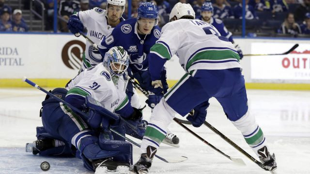 Vancouver-Canucks-goaltender-Anders-Nilsson-(31)-makes-a-pad-save-on-a-shot-by-Tampa-Bay-Lightning-center-Vladislav-Namestnikov-(90)-during-the-second-period-of-an-NHL-hockey-game-Thursday,-Feb.-8,-2018,-in-Tampa,-Fla.-Canucks-defenseman-Christopher-Tanev-(8)-looks-on.-(Chris-O'Meara/AP)
