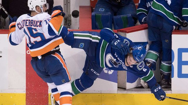 New-York-Islanders-right-wing-Cal-Clutterbuck-(15)-checks-Vancouver-Canucks-right-wing-Brock-Boeser