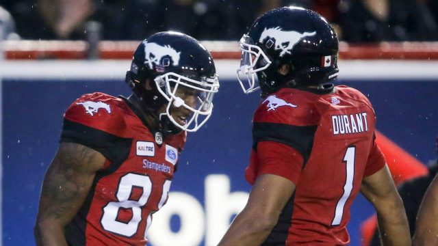 Calgary-Stampeders'-Kamar-Jorden,-left,-celebrates-his-touchdown-with-teammate-Lemar-Durant,-during-second-half-CFL-football-action-against-the-Ottawa-Redblacks-in-Calgary,-Thursday,-June-28,-2018.