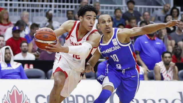 Canada's-Andrew-Nembhard-goes-to-the-basket-against-Dominican-Republic's-Rigoberto-Adris-Geraldo-De-Leon-Jimenez,-right,-during-their-FIBA-Basketball-World-Cup-Qualifier-game-in-Toronto,-Friday-June-29,-2018.