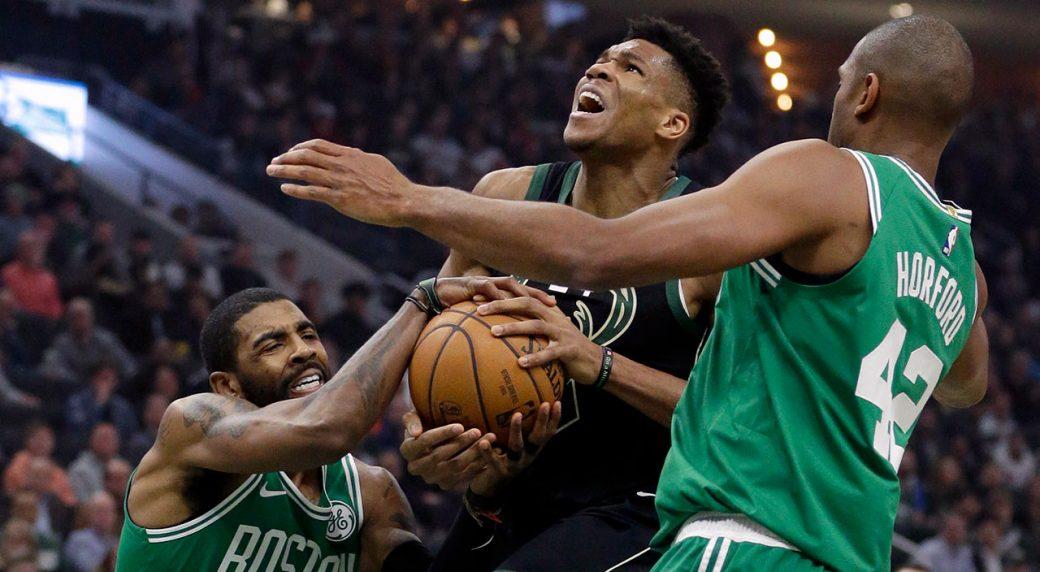 ae8d9c4b06b5 Boston Celtics  Kyrie Irving (11) forces a jump ball against Milwaukee  Bucks  Giannis Antetokounmpo